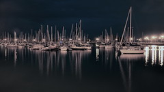 Harbor Reflections (Seth Oliver Photographic Art) Tags: nightphotography chicago reflections boats landscapes illinois nikon midwest cityscapes lakemichigan uptown nightshots harbors montroseharbor pinoy circularpolarizer urbanscapes secondcity monochromes windycity longexposures chicagoist d90 nightexposures wetreflections cityofbigshoulders setholiver1 tripodmountedshot 1024mmtamronuwalens timedelaytriggeredshot