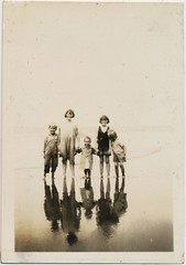 Take your ghosts to the seaside (liquidnight) Tags: old family blackandwhite bw beach water monochrome sepia kids sisters vintage reflections children fun found happy photo seaside distorted brothers antique snapshot smiles happiness eerie siblings adventure collection together photograph shore vernacular haunting ghosts holdinghands recreation ghostly carefree outing handinhand foundphotos