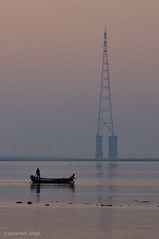 early morning scene at The Ganges (gurpreet_singh.) Tags: morning reflection tower water silhouette sunrise river dawn boat high twilight earlymorning electricity shallow rise transmission boatman ganga ganges yamuna