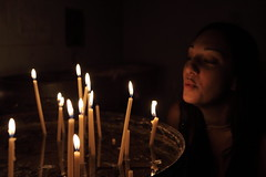 Prayers and wishes (Elios.k) Tags: light shadow portrait reflection church girl horizontal dark temple focus candles candle religion blowing chapel depthoffield indoors greece burning flame monastery getty inside shallow tradition orthodox oneperson extinguish monodendri epirus zagori agparaskeyi subgetty