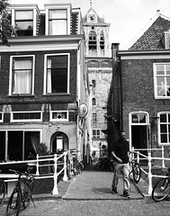 Alley (alideniese) Tags: delft southholland thenetherlands streetphotography stadhuisdelft blackandwhite bw man person bridge bikes buildings architecture old alley alleyway