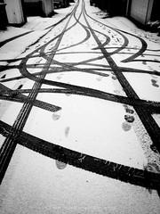 spin out (bluechameleon) Tags: street winter blackandwhite bw snow abstract detail vancouver alley pattern backalley hill curves tracks footprints eastside emptiness eastvancouver tiretracks garagedoors bluechameleon artlibre sharonwish bluechameleonphotography ofportalsandparallelworlds