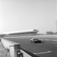 G55 races past the pitlane (Julian Dyer) Tags: blackwhite racing silverstone motorsport ginetta ilfordfp4 ilfordddx homedevelopment homeprocessing mamiyac330f silverstonenational ginettamediaday2013