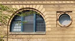 Two Windows (sharon'soutlook) Tags: cincinnati oh windows portholewindow arched bricks brickwork building tree blinds basrelief