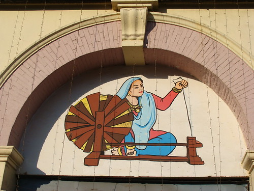 Woman spinning a Charkha  A mural atop the entrance of Shri