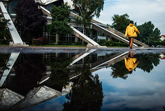 331/365  Arena (ewitsoe) Tags: ewitsoe puddle man walking yellowraincoat rain summer storm architecture communist arena old structure sky nikond80 35mm street yellow pool water warm trees reflected mirror poznan poland brutalism