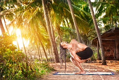 Yoga twisted pose (Pasasana) by HAWAH on the beach near the fishermen hut in Varkala, Kerala, India.