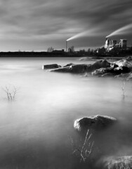 High water (- David Olsson -) Tags: longexposure blackandwhite bw plants lake seascape industry water monochrome clouds landscape mono nikon rocks factory cloudy sweden branches smoke tripod january windy newyear cliffs le pollution firstday grayscale sunlit chimneys vnern 2012 dx hammar vrmland 1635 sidelit naturevsman ndfilter 1635mm lakescape smoothwater skoghall smoothsky environmentaldegradation 2exposures d5000 manualblend manuallyblended davidolsson nd500 lightcraftworkshop 1635vr grytudden