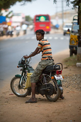 CHENNAI, INDIA-FEBRUARY 13: Boy on a motorcycle on February 13, 2013 in Chennai, India. Boy on a motorcycle on the streets of Chennai. (Sergey Mikushev) Tags: hinduism india asia asian backgrounds bike boy bus cheerful child childhood children childs culture ethnicities friendship heat hindu indian loock looking motobike people south street subcontinent summer vertical