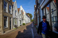 Man with hat @ Gouda (PaulHoo) Tags: gouda holland netherlands fuji x70 city urban citylife candid streetcandid streetphotography 2016 blue hat fashionable men man reflection architecture shadow contrast