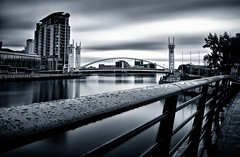SALFORD QUAY BLUES.  (Explore) (Neil Hulme.) Tags: longexposure blue blackandwhite motion water monochrome river lumix mono cityscape fineart bridges salfordquays ndfilter daytimelongexposure nd110filter blackandwhitelongexposure