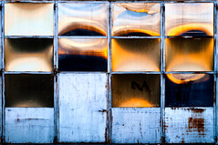 the sun plays checkers (toleman.hart) Tags: door old light italy abstract france detail reflection window glass metal horizontal architecture geotagged interestingness nikon europe italia geometry steel rusty nobody minimal retro warehouse emilia explore vision backgrounds abstraction 2012 emiliaromagna reggio reggioemilia absence toleman pianurapadana explored cavriago d5000 tolemanhart visionquality1000