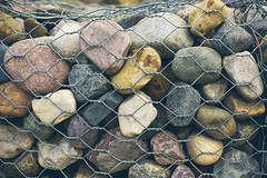 Caged Surfaces (TerryJohnston) Tags: mi wire rocks dof br bokeh michigan cage textures riverrocks bigrapids amazingmich canoneos5dmarkiii 5dmarkiii