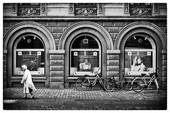 Catching the light (anologital) Tags: street old trip blue white black hat stone lady 35mm copenhagen theatre roman bikes olympus elderly hp5 archway cobbles ilford