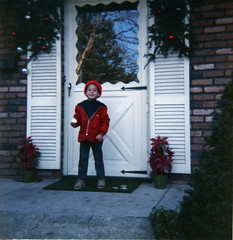 Bobby eating an apple in front of the Christmas decorations (epicharmus) Tags: christmas door family boy ny newyork reflection tree home apple pine mailbox kid child kodak eating bricks decoration longisland jacket cap ornaments shutters poinsettias 1972 doormat shrubs 1973 frontdoor columbusavenue nassaucounty bellmore daddino northbellmore thebellmores robertdaddino processedjanuary141973 12612negative