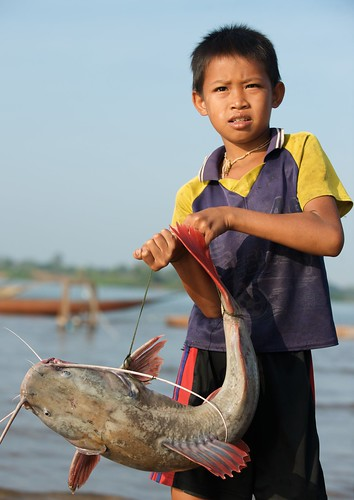 Boy carrying fish to market, Khone Falls, Laos. Photo by Patrick Dugan, 2009.