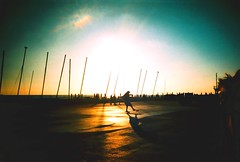 manualing (fotobes) Tags: sky man sunshine silhouette boats lca xpro crossprocessed brighton shadows sails skateboard hood vignetting afternoonsun skateboarder brightonseafront manualing rolleidigibasecr200