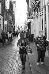 Brunette holding camera (Wookiee!) Tags: girl girls woman women feminine venus beauty pretty she candid street city urban life sneaky unposed unpolished bw blackandwhite monochrome streetview centre capital amsterdam 020 people human lens 35mm canon d550 raw summer hot warm 17 august 2016 wednesday xxx the netherlands holland dutch obsessive photograpy streetphotography straatfotografie amateur sharp prime nl noordholland day light sun sunny strangers wwwgevoeligeplatennl