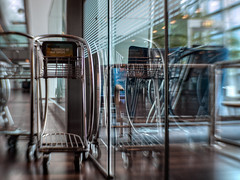 Chrome and Glass (Anne Worner) Tags: anneworner copenhagen kastrup lensbaby reflections sweet35 airport bend bendy blur bokeh curves floor glass glitzy horizontal lines luggagecarts modern shiny steel vertical window woodenfloor