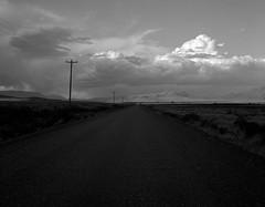 Along a Road, Eastern Oregon (austin granger) Tags: oregon alvorddesert gravelroad telephonepoles lastlight storm clouds gf670