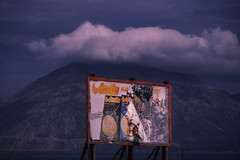 Archive  Patras March 1985 (i_shudder) Tags: sky cloud mountain sign landscape decay symmetry billboard greece patras