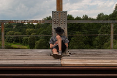 Modern Day Cowboy (modestmoze) Tags: cowboy man sitting relaxing sky clouds white blue grey brown black shirt hat shorts planks wood wooden 2016 summer july outside outdoors day 500px lines tracks traintracks view travel bridge old architecture metal railings green