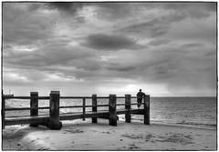 longing... (kurtwolf303) Tags: woman frau monochrome outdoor himmel sky meer sea ocean water wasser wolken clouds dramatic dramatisch rahmen olympusem1 omd microfourthirds micro43 ufer sw bw shore person unlimitedphotos 250v10f topf25 topf50 500v20f topf75 topf100 750views systemcamera 800views 1000v40f unescoweltnaturerbewattenmeer föhr insel island wyk topf150 steg nordfriesland 1500v60f mft kurtwolf303