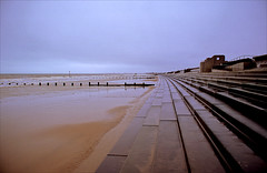 the seaside town that summer forgot (Ron Layters) Tags: winter sea england cold reflection beach water geotagged kent sand pentax unitedkingdom empty steps overcast slide seawall velvia transparency seafront fujichrome groyne pentaxmz10 dymchurch romneymarsh novisitors shepway ronlayters slidefilmthenscanned mz10 geo:lat=5102316508773013 geo:lon=09949116451831408 horizonenglishchannel