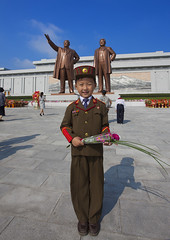 Kid In Army Uniform Paying Respect To The Two Statues Of The Dear Leaders In Grand Monument Of Mansu Hill, Pyongyang, North Korea (Eric Lafforgue) Tags: portrait people flower color colour men statue vertical standing asian soldier army official war asia day propaganda anniversary military politics father bluesky visit korea celebration forbidden kimjongil government asie former copyspace