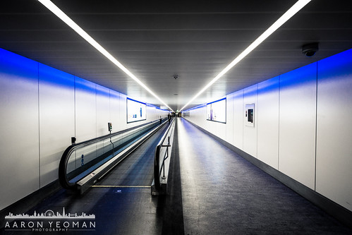 lighting city uk greatbritain travel blue shadow england people urban holiday reflection london lines architecture reflections person lights vanishingpoint europe shadows westsussex unitedkingdom corridor terminal symmetry line walkway gb symmetrical vignetting vignette adverts crawley a77 travelator terminal2 terminal1 lgw gatwickairport converginglines fluorescentlamp sigma1020mm1456exdchsm sonya77 slta77 sonyalphaslta77