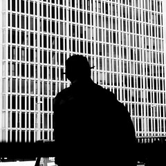 Up Against The Wall (petertandlund) Tags: street city shadow people urban blackandwhite bw man blancoynegro monochrome hat silhouette backlight square pattern graphic sweden stockholm streetphotography sergelstorg sthlm bnw norrmalm flickrfriday xe1 fujix sergelskraporna