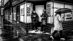 The only dry corner in town. (Mister G.C.) Tags: blackandwhite bw image streetshot streetphotography photograph monochrome urban town city rain raining rainy umbrella women ladies doorway zonefocus zonefocusing snapfocus ricoh ricohgr pointshoot mistergc schwarzweiss strassenfotografie scotland britain greatbritain gb british uk unitedkingdom europe