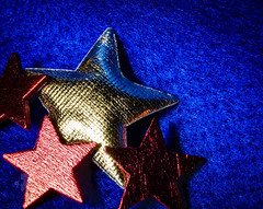 Coloured Stars (DeePee64) Tags: stars macro bluebackground bluefelt fabricstar cardboardstar redstar goldstar christmascardmakingmaterials