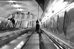 The Daily Grind (Nicola Riley) Tags: city uk england blackandwhite bw london monochrome up canon underground movement workers escalator tube streetphotography down daily noflash passengers tubestation londonunderground dailygrind descending ascending 18200mm 60d canon60d 18200efs nicolariley