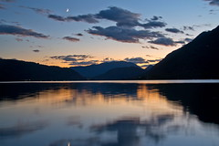 Evening with moon at the Ossiach lake, Carinthia, Austria (echumachenco) Tags: evening sunset blue pink sky clouds moon sickle lake water reflection mountain silhouette alps outdoor dobratsch ossiach ossiachersee carinthia krnten austria sterreich september nikond3100