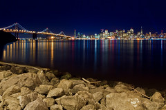 Artificial Lights [Explored] (boingyman.) Tags: sf sanfrancisco longexposure bridge light reflection night canon landscape rocks cityscape treasureisland nightscape baybridge scape ti 1022 artificiallight t2i boingyman
