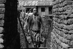 Over the bridge, under the rainbow (zounix / eye in motion) Tags: old bridge nepal portrait people woman mountain nature monochrome face dof bokeh walk mother photojournalism nb regards reportage shakti blackwhitephotos zounix