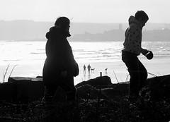 Heading back (farwest56) Tags: uk boy sea england people blackandwhite bw woman dog sun beach water silhouette skyline walking 50mm mono sand couple cornwall sony shoreline wave seashore penzance mountsbay a350 sal50f14