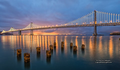 San Francisco - Bay Lights at Twilight (Panorama) (Darvin Atkeson) Tags: show sanfrancisco california white storm reflection art water lights coast moving artwork skies glow dancing pacific bright suspension display artistic anniversary pastel stormy illuminated led celebration cables baybridge bayarea 75 75th citybythebay darvin atkeson darv liquidmoonlightcom