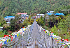 Suspension bridge with prayer flags  in village of Jorsale , Himalayan region of Sagarmatha National Park, Nepal (marozn) Tags: sherpa himalaya everest nepal mountains himalayan hiking adventure trail stone outdoor india road climbing rock trek mountaineer walking route trekking high outdoors nature landscape bridge flags asia asian expedition flag jorsale anger dangerous mount forest houses trees across architecture canyon crossing nepali over rope valley view transportation