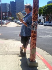 stock  Reading A Book Against Telephone Pole (Lynn Friedman) Tags: street print reading book waiting graphic ad front financialdistrict embarcadero zebra leisure vallejo telephonepole 94111 embarcaderocenter lynnfriedman