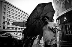 Wind and Rain Can't Stop Me (stimpsonjake) Tags: nikoncoolpixa 185mm streetphotography bucharest romania city candid blackandwhite bw monochrome umbrella wind rain man