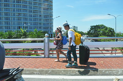 Doing it the hard way (Roving I) Tags: couples travellers friends tourists tourism suitcases baggage luggage backpacks sunhats walking azura apartments homes bridges danang vietnam