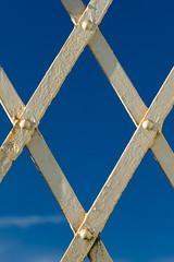 Footbridge (mikeplonk) Tags: bridge footbridge trefforest pontypridd southwales diamond parallelogram blue white sky cloud cpl polarisingfilter polarizingfilter arrivatrainswales trenauarrivacymru nikon d5100 18140mm closeup abstract minimal minimalist minimalism symmetry symmetrical iron rust