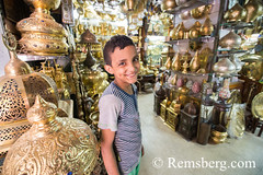 Cairo, Egypt. Young Egyptian boy standing in a shop selling ornate gold pots and vases in the outdoor bazaar/ flea market Khan el-Khalili in Cairo. (Remsberg Photos) Tags: africa cairo middleeast egypt world travel sightseeing tourist photography desert egyptian children young boy bazaar market purchase buy sell colorful culture barter fleamarket streetmarket outdoor gold vases pots ornate egy