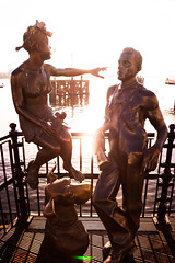 Bronze Glow (ShaunHill.net) Tags: life summer portrait people woman dog sun white man black men monument girl statue sepia lady bronze fence landscape person photography mono amber fly photo mutt friend warm glow glare bright sunny photograph figure flare feeling striking figures tone shaunhillphotography