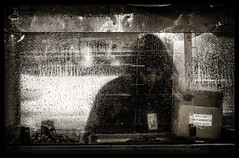 The Ghost in The Machine (Feldore) Tags: street food man wet glass rain square sony mysterious raindrops vendor times behind raining ghostly mchugh drizzle hooded rx100 feldore