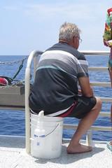 bucket seat (BarryFackler) Tags: fairwindcruises fairwindii fairwind snorkelcruise snorkeling boat hawaii kealakekua kealakekuabay hawaiiisland bigisland nautical hawaiicounty saltwater westhawaii aquatic marine sea bay outdoor ocean island tropical water sandwichislands vacation tourists pacificocean hawaiianislands kona southkona konacoast barryfackler barronfackler bucket spraybottle sitting railing chain horizon man kane outdoors polynesia pacific life people 2016 swimtrunks boardshorts