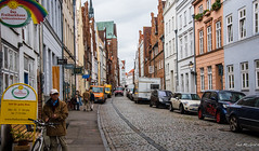 2016 - Baltic Cruise - Lbeck Germany - Street Scene (Ted's photos - For Me & You) Tags: 2016 cropped germany lubeck tedmcgrath tedsphotos vignetting lbeckgermany unesco unescoworldheritagesite streetscene street people peopleandpaths cobblestones bicycle ballcap signs vehicles