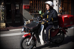 Kobe delivery time! (Eric Flexyourhead) Tags: street city red urban woman blur bike japan honda japanese motorbike kobe jp motorcycle delivery 日本 kansai vignette hyogo supercub chuoku postalworker hondasupercub 兵庫県 中央区 japanpost 神戸市 kobeshi 関西地方 olympusep1 slrmagic26mmf14toylens